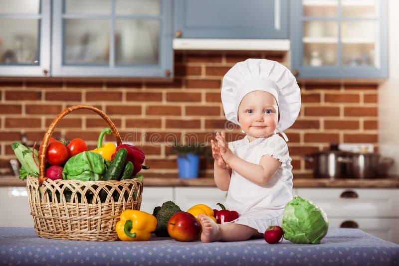 O bebê de sorriso vestiu-se no toque e no avental brancos do cozinheiro chefe imagens de stock