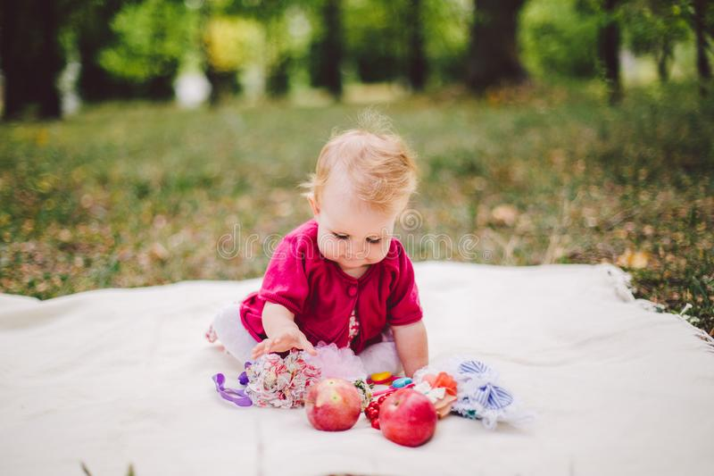 O bebê de um ano louro da afiliação étnica caucasiano pequena do bebê do nascimento senta-se em uma manta na grama verde no parqu foto de stock royalty free