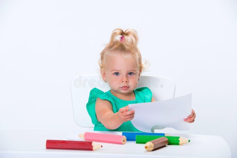 O bebê de um ano louro pequeno bonito do bebê está tirando com os lápis coloridos grandes isolados no fundo branco Desenvolviment fotos de stock royalty free