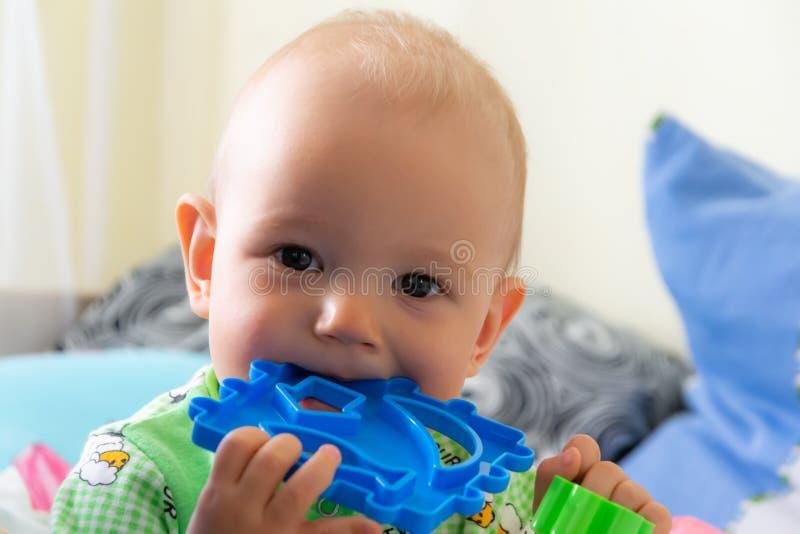 O bebê de um ano rói um brinquedo plástico porque seu sair os dentes Menino alegre pequeno em uma luz - terno verde com carneiros imagens de stock