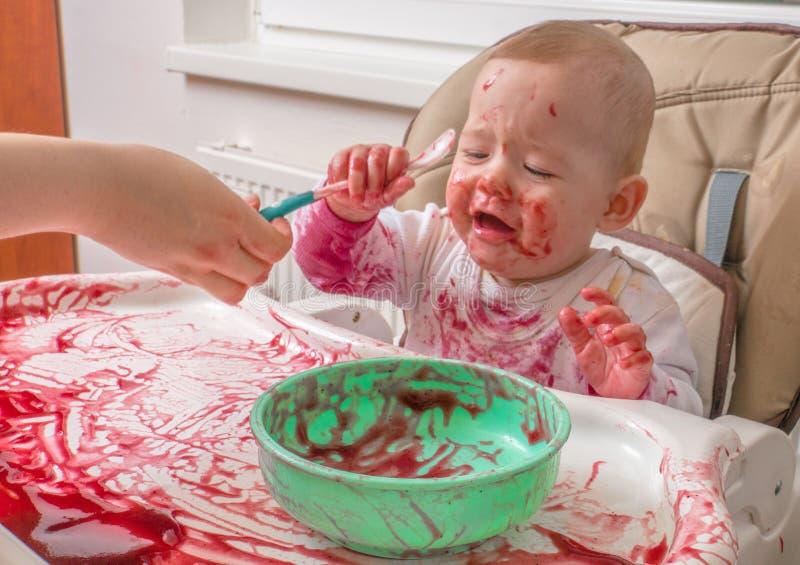 O bebê desarrumado e sujo está comendo e está gritando imagens de stock