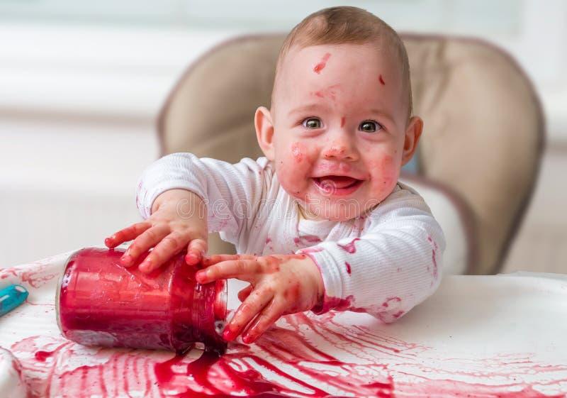 O bebê desarrumado e sujo está comendo o petisco com mãos fotografia de stock