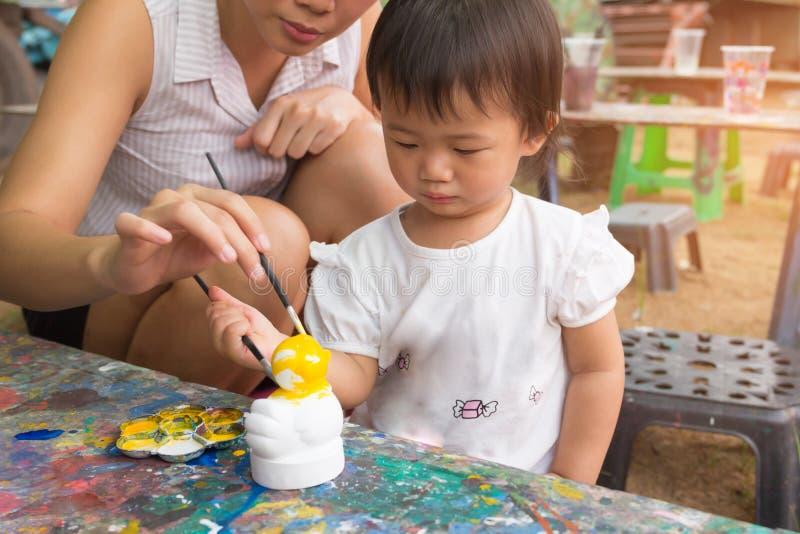 O bebê e a mãe bonitos asiáticos da menina estão pintando colorido fotos de stock