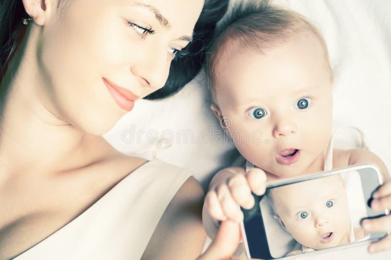 O bebê e a mãe engraçados fazem o selfie no telefone celular imagem de stock