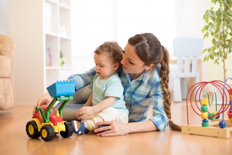 O bebê e a mamã pequenos jogam no assoalho com brinquedo do trator imagens de stock