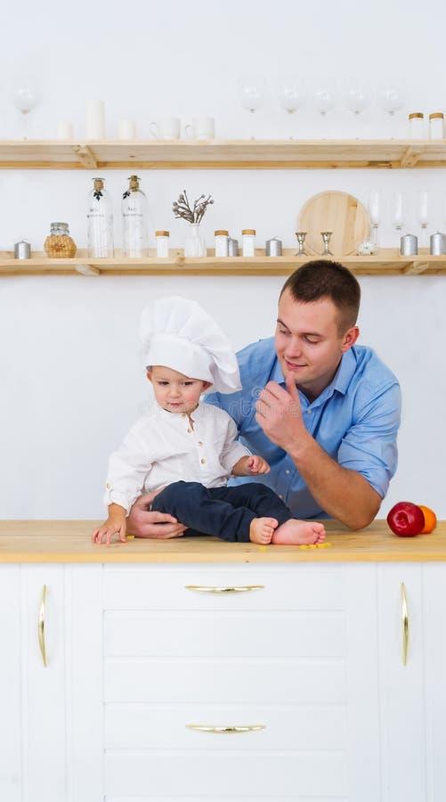O bebê e o pai novo estão na cozinha na tabela Paizinho feliz da família, filho pequeno no tampão do cozinheiro foto de stock