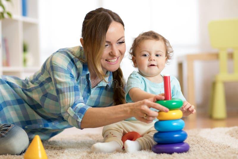 O bebê e sua mamã jogam com brinquedos em casa fotos de stock