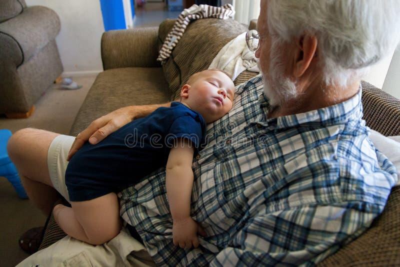 O bebê em um Onsie passou para fora adormecido na caixa de seu Grandf imagem de stock