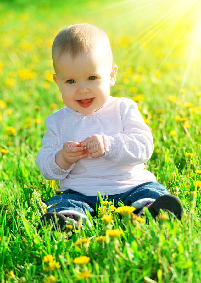 O bebê em um prado verde com amarelo floresce dentes-de-leão no th fotografia de stock royalty free