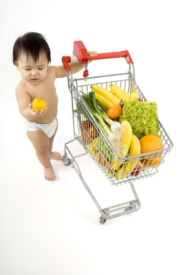 O bebê empurra um carro de compra fotos de stock
