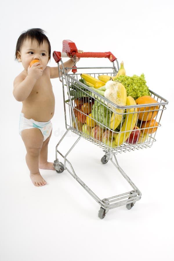 O bebê empurra um carro de compra fotografia de stock royalty free