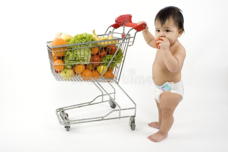 O bebê empurra um carro de compra imagem de stock royalty free