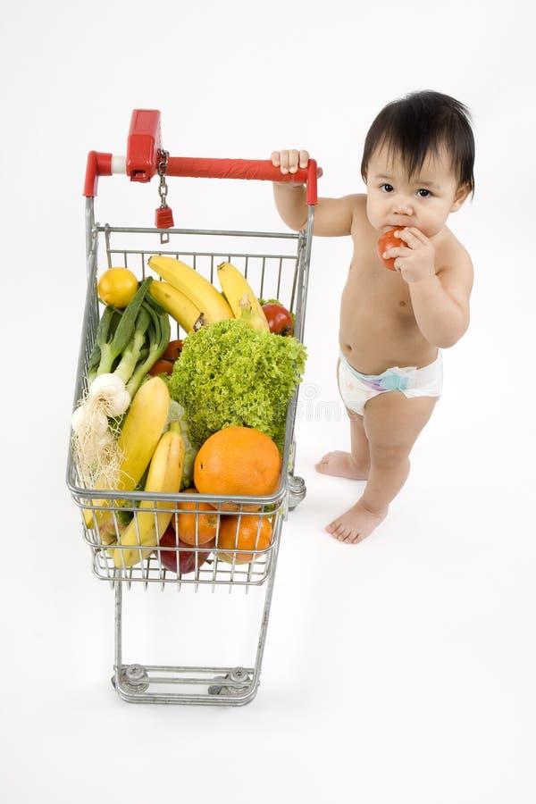 O bebê empurra um carro de compra fotografia de stock