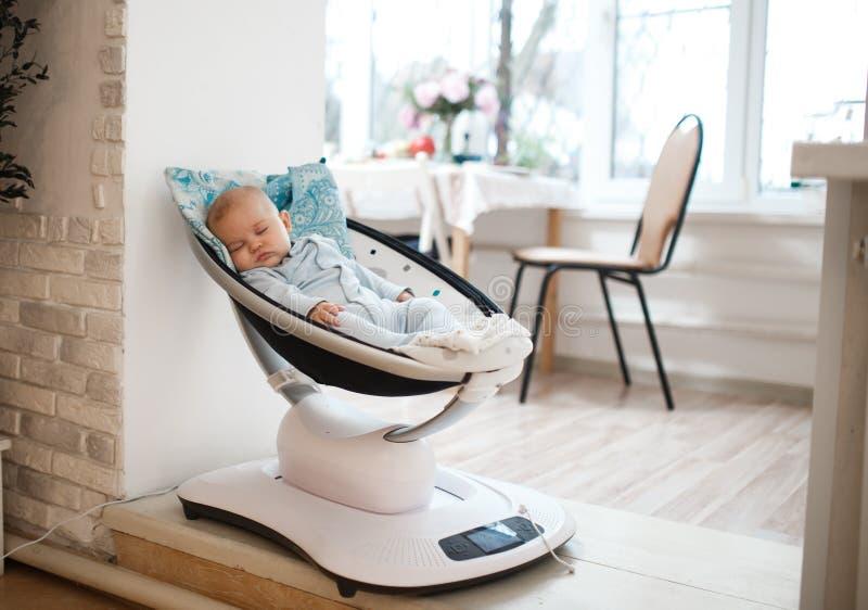 O bebê encontra-se em um carrycot automático na sala clara fotos de stock