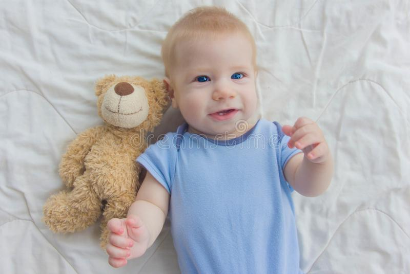 O bebê encontra-se no assoalho com um urso de peluche Uma ondulação da criança sua fotografia de stock royalty free