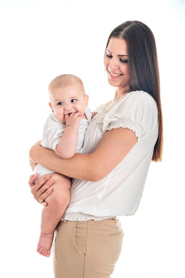 O bebê era de grito e mordendo seus dedos, escale os primeiros dentes Imagem da mãe feliz com infante adorável fotografia de stock