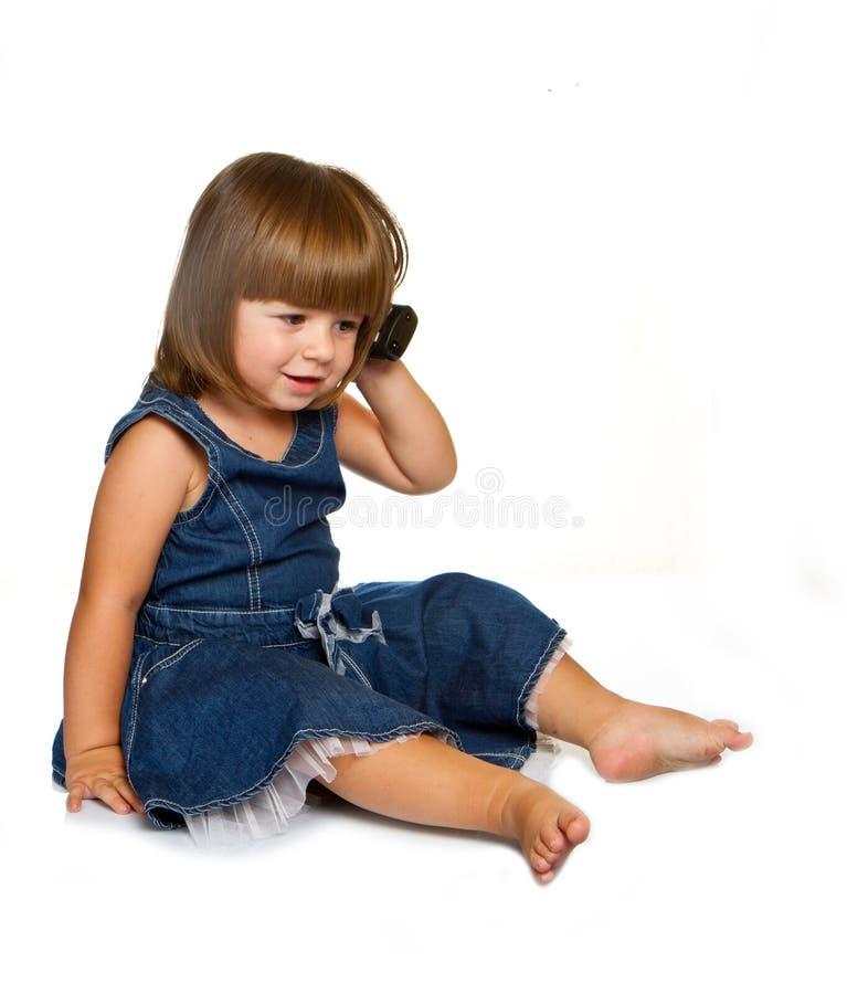 O bebê está falando no telemóvel, isolado sobre o branco foto de stock