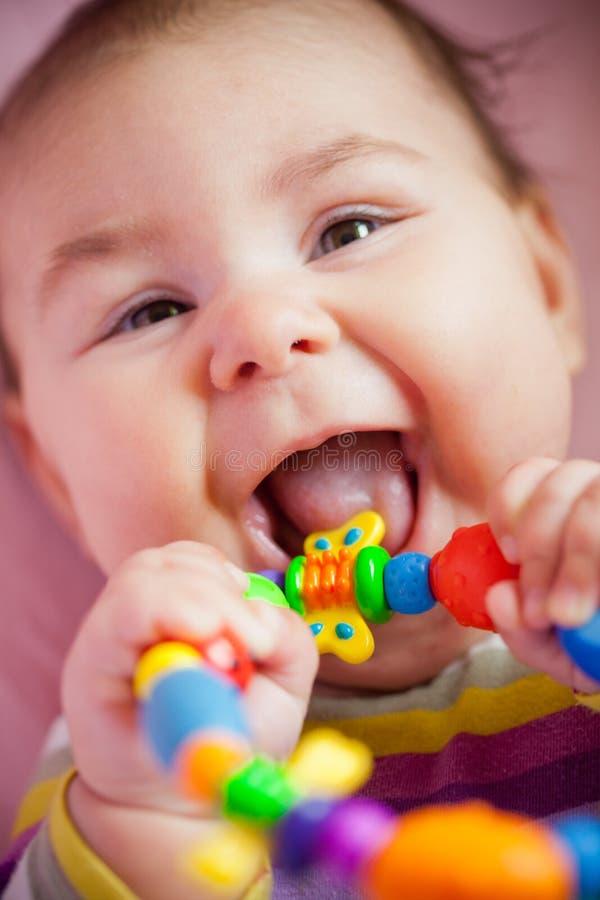 O bebê está rmoendo um brinquedo imagem de stock