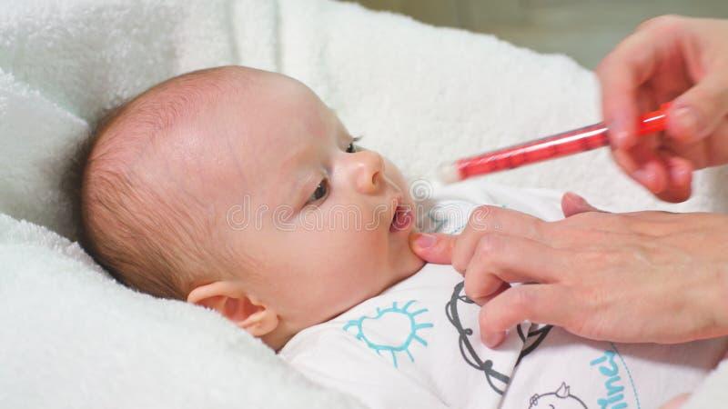 O bebê está tomando a medicina por uma seringa imagens de stock