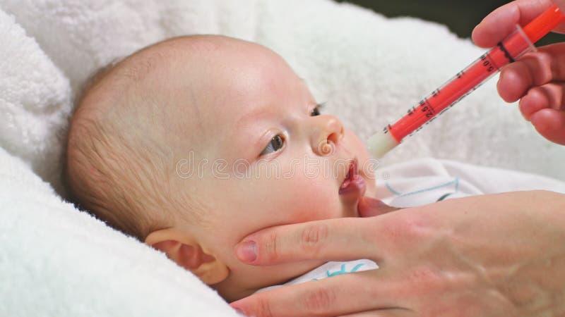 O bebê está tomando a medicina por uma seringa foto de stock