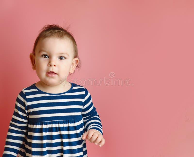 O bebê feericamente pequeno adorável sente bom e sorriso no rosa fotografia de stock royalty free