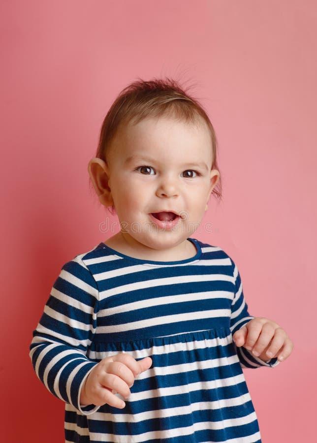 O bebê feericamente pequeno adorável sente bom e sorriso no rosa imagens de stock royalty free