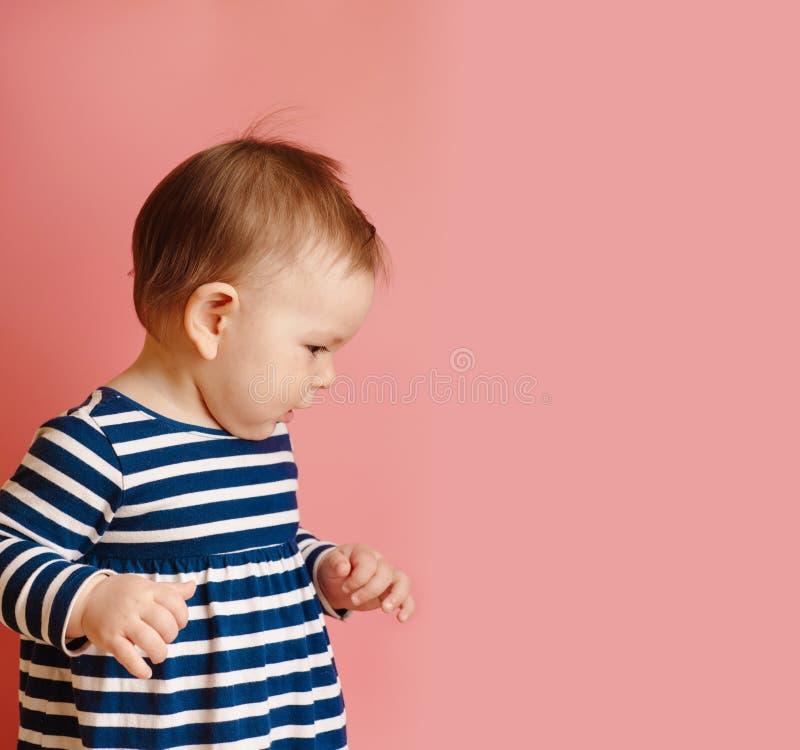 O bebê feericamente pequeno adorável sente bom e sorriso no rosa foto de stock