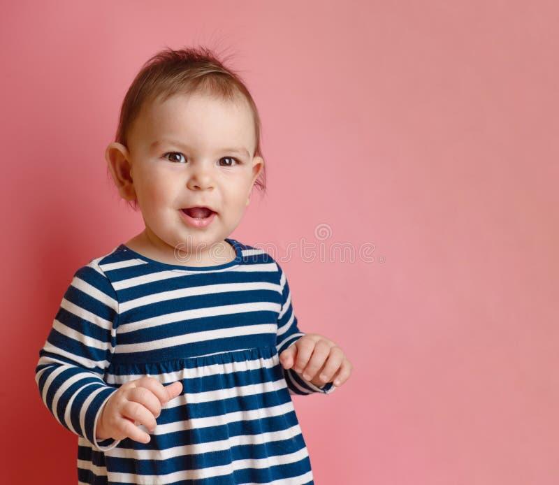 O bebê feericamente pequeno adorável sente bom e sorriso no rosa fotos de stock royalty free