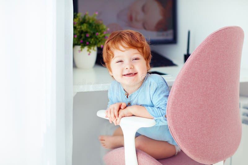 O bebê feliz da criança do ruivo está sentando-se na cadeira do escritório no lugar de funcionamento imagem de stock