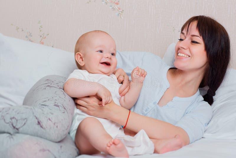 O bebê feliz joga com o mum nos pijamas na cama, no riso e na manutenção programada fotografia de stock