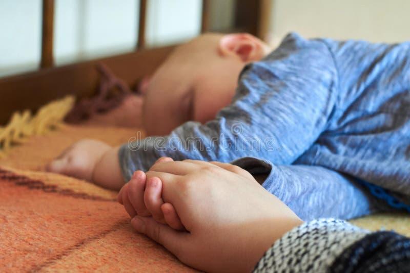 O bebê guarda a mão da sua mamã ao dormir fotos de stock royalty free