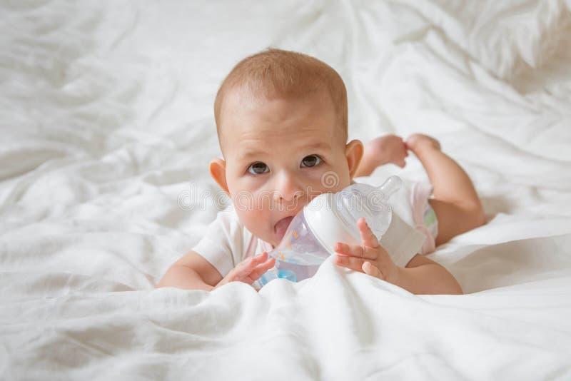 O bebê infantil com os olhos marrons grandes que encontram-se na cama branca e lambe a garrafa especial da água com bocal Tenta r imagens de stock royalty free