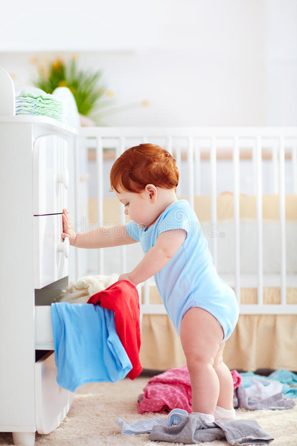 O bebê infantil engraçado que joga para fora veste-se do armário em casa imagem de stock
