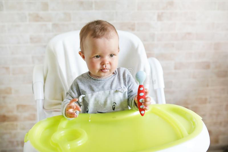 O bebê infantil feliz com colher come-se em casa na cozinha ensolarada alimento da nutrição para crianças imagem de stock royalty free