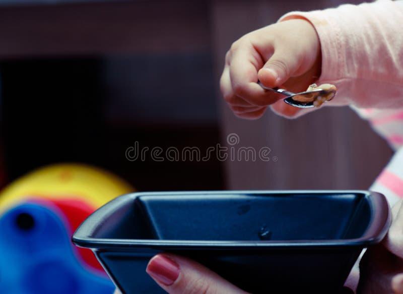 O bebê infantil guarda a colher come o alimento próprio imagens de stock