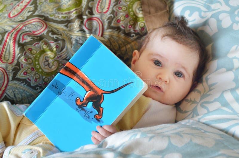 O bebê infantil leu um livro fotos de stock royalty free