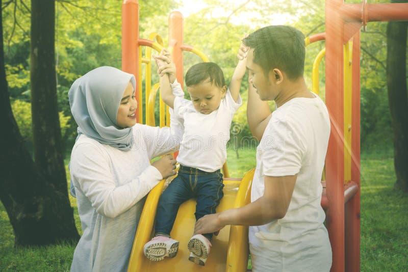 O bebê joga em uma corrediça com seus pais foto de stock