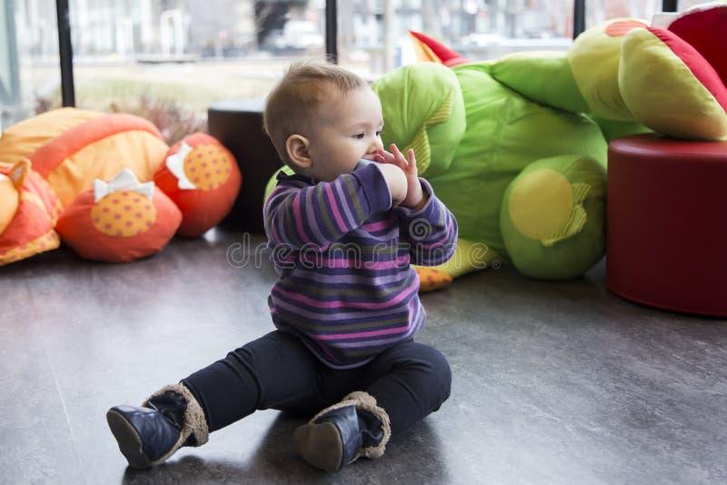O bebê justo bonito que senta-se na sala de jogos no metade-perfil no assoalho com um pé estendeu a sugação no brinquedo imagens de stock royalty free