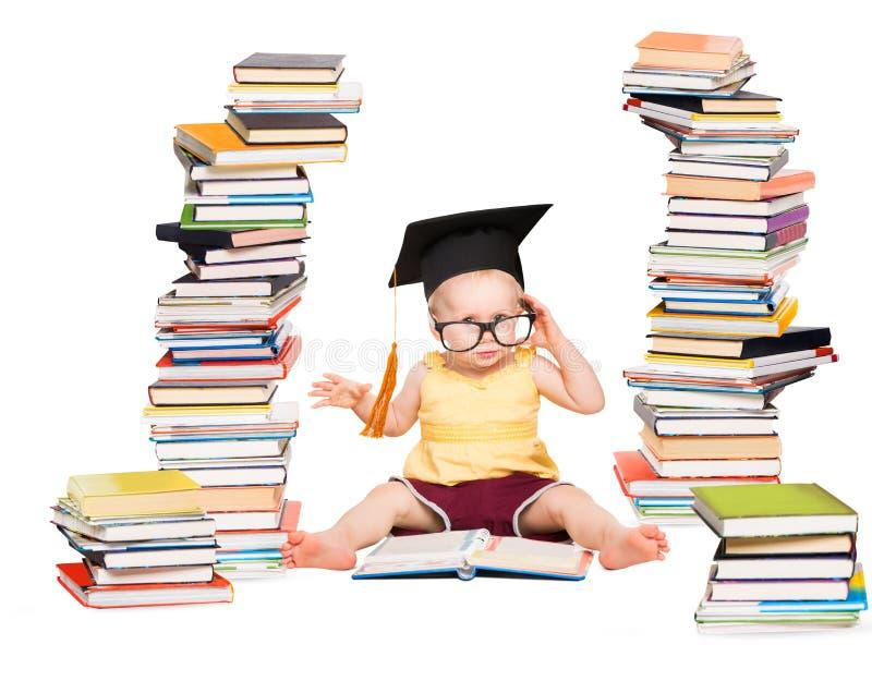 O bebê leu o livro no chapéu da graduação e nos vidros, criança esperta no branco imagens de stock royalty free