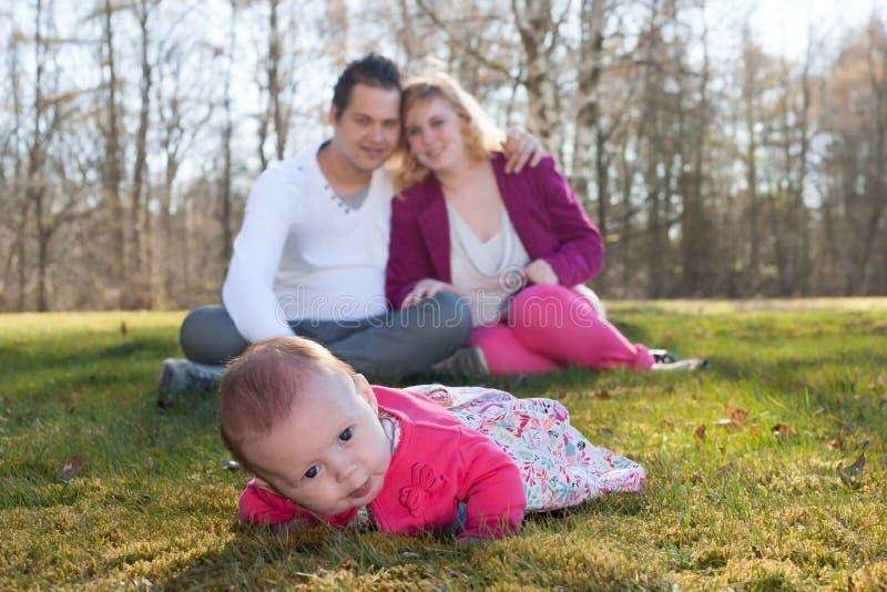 O bebê na grama parents no fundo fotografia de stock royalty free