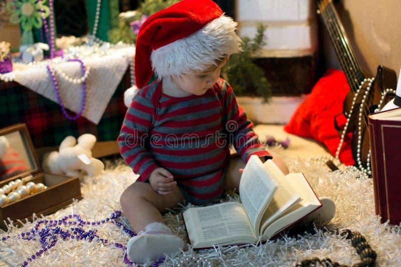 O bebê no chapéu de Santa leu um livro fotos de stock