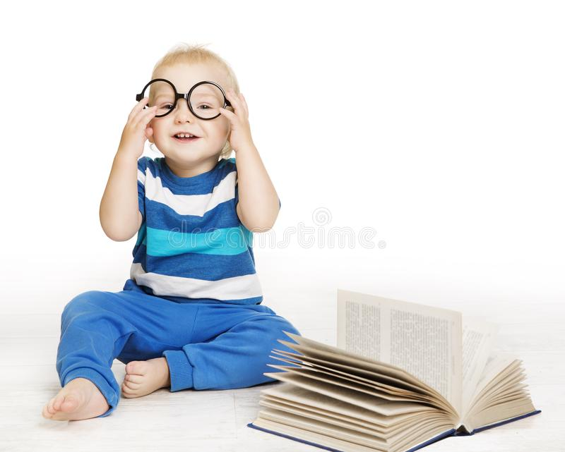 O bebê nos vidros leu o livro, crianças adiantadas educação, criança no branco fotografia de stock