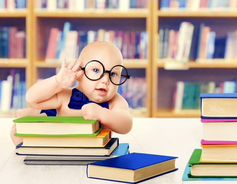 O bebê nos vidros leu livros, desenvolvimento esperto da educação da criança fotografia de stock