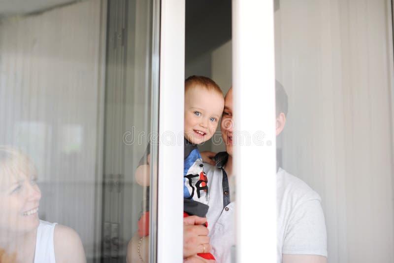 O bebê olha através de uma quebra de uma janela aberta imagens de stock royalty free