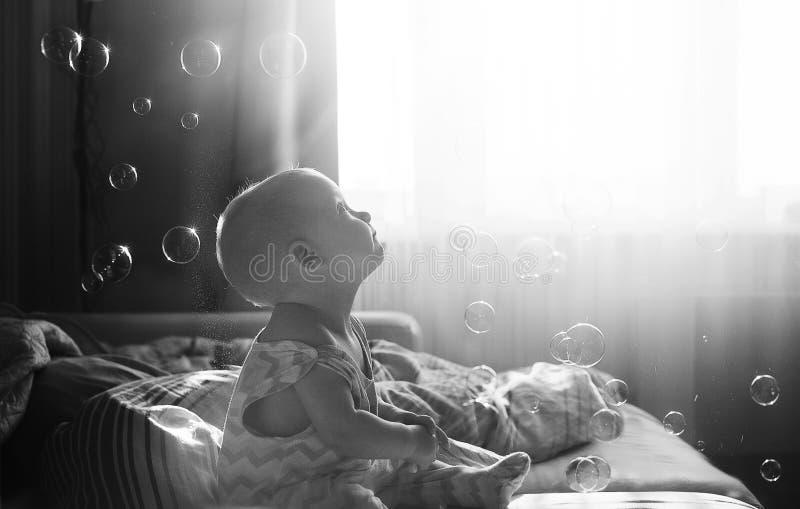 O bebê pequeno bonito engraçado olha bolhas de sabão na sala Filtro de tonificação preto e branco do instagram Conceito feliz da  fotografia de stock royalty free