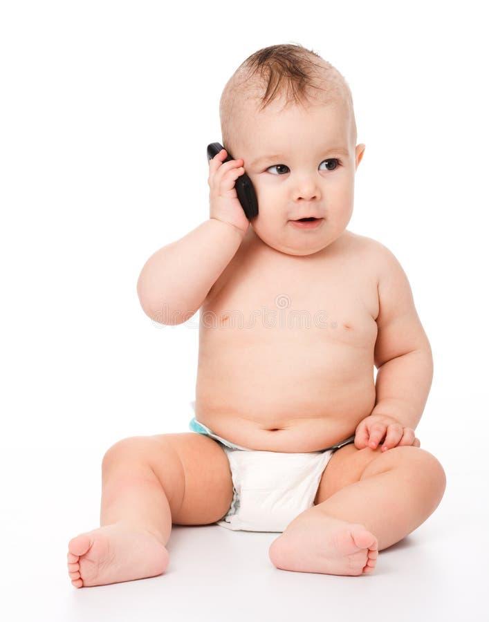 O bebê pequeno bonito está falando no telefone de pilha imagem de stock royalty free