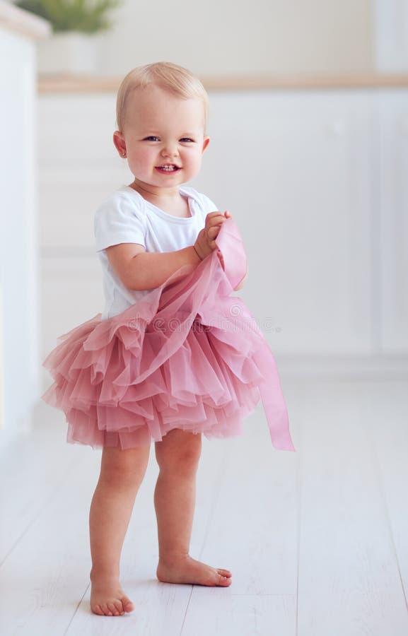 O bebê pequeno bonito na saia do tutu está no assoalho em casa fotografia de stock royalty free