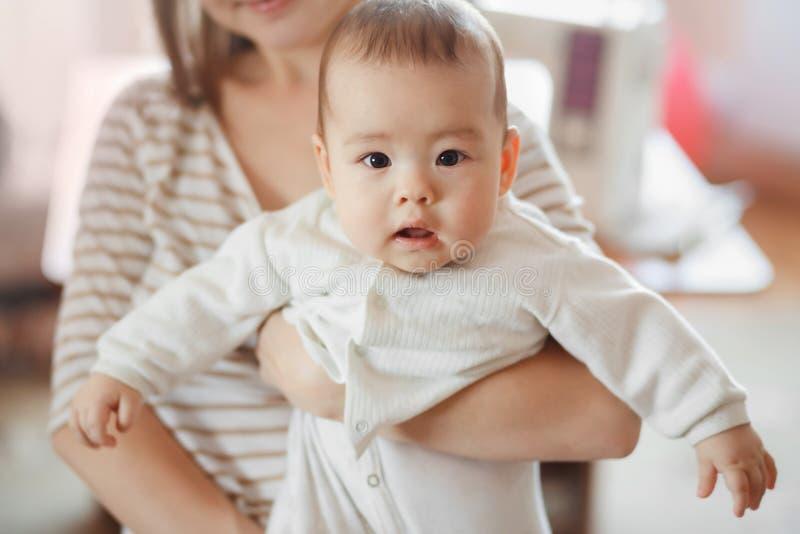 O bebê pequeno bonito nos braços da mamã no ar Mãe e infante, cuidado infantil, crescimento das crianças Interessada olhares fotografia de stock royalty free