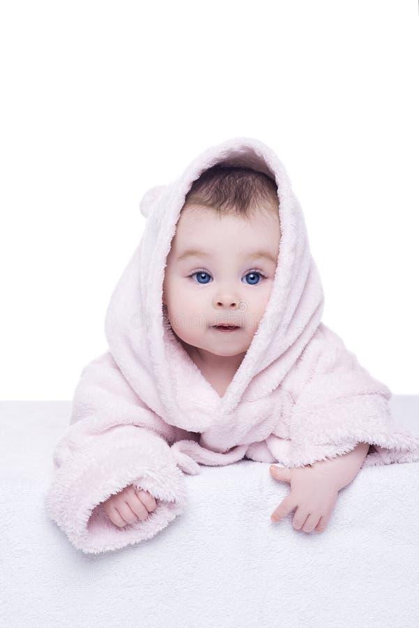 O bebê pequeno com olhos azuis no roupão cor-de-rosa que encontra-se nela seja foto de stock
