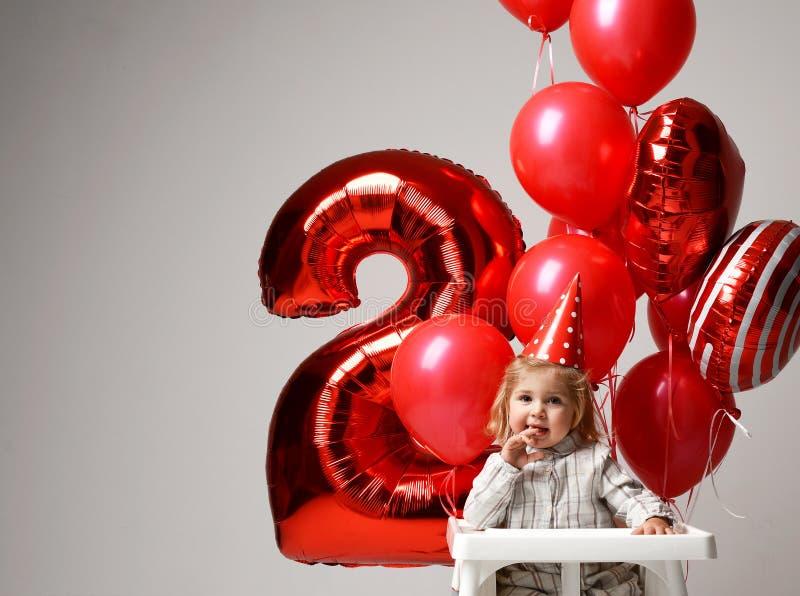 O bebê pequeno comemora seu segundo aniversário com bolo doce o fotografia de stock